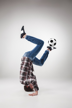 Portrait  of young man, practicing yoga with football ball on gray background. concept of continuous soccer practice