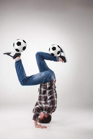 meditator: Portrait  of young man, practicing yoga with football balls on gray background. concept of continuous soccer practice Stock Photo