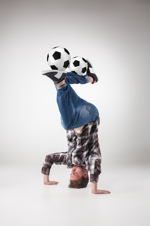 Portrait  of young man, practicing yoga with football balls on gray background. concept of continuous soccer practice Stock Photo