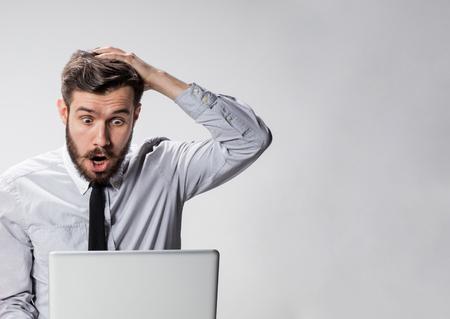 Il giovane uomo sorpreso con il suo computer portatile su sfondo grigio