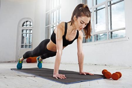Hermosas jóvenes delgados mujer haciendo flexiones en el gimnasio con pesas naranja
