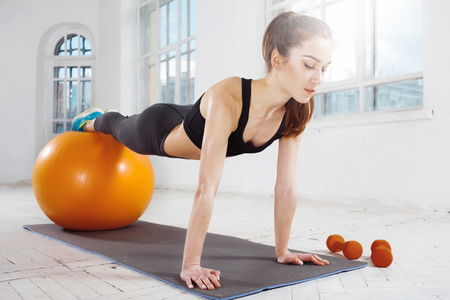 plasticity: Beautiful young slim woman doing some gymnastics at the gym with fitball Stock Photo