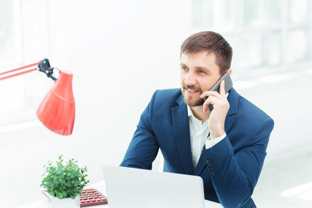 phonecall: Portrait of businessman talking on mobile phone in office