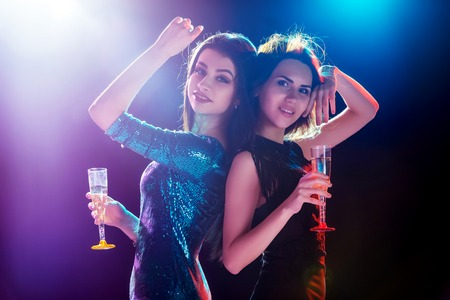 dancing club: Party, holidays, celebration, nightlife and people concept - smiling young beautiful girls dancing in club