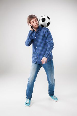 the admirer: A portrait of a fan with ball, holding a phone on white background Stock Photo