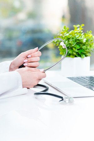preventative: The female doctor with a stethoscope in the hands against laptop Stock Photo