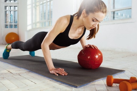 plasticity: Beautiful young slim woman doing some gymnastics at the gym with medball Stock Photo
