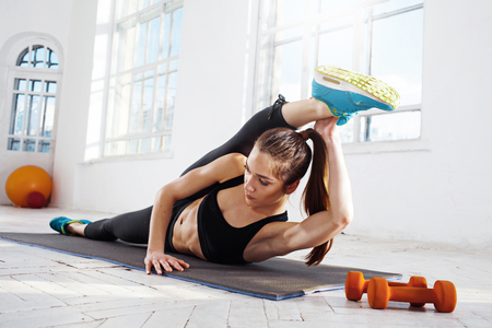 plasticity: Beautiful young slim woman  doing stretching exercises at the gym with orange dumbbells