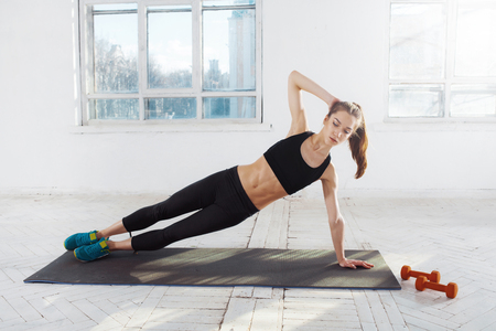 plasticity: Beautiful young slim woman  doing push ups at the gym with orange dumbbells
