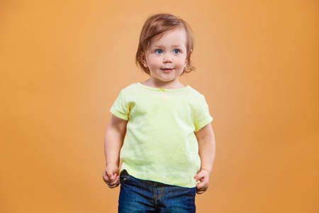 innocent: One cute and funny baby girl on orange background