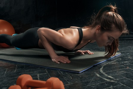 plasticity: Beautiful young slim woman doing push ups at the gym