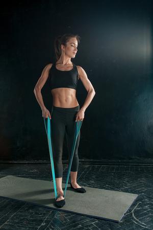 ゴムバンドでジムでストレッチ体操を行う若いスリム美人