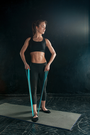 plasticity: Beautiful young slim woman doing stretching exercises at the gym with a rubber band