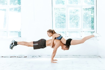 plasticity: The fit woman and man doing some push ups at the gym on white background Stock Photo