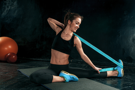 The brunette athletic woman exercising with rubber tape on black wooden floor Imagens