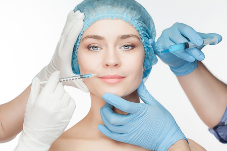 Attractive woman at plastic surgery with syringe in her face on white background Imagens