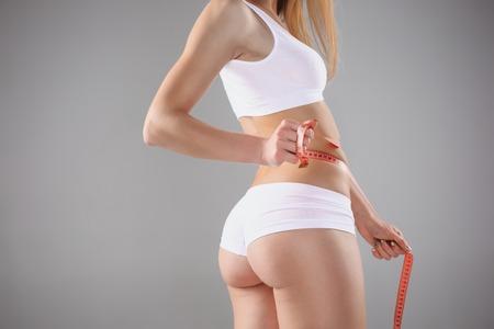 Mooi meisje in witte lingerie die blauwe meter houden die perfecte vorm van haar mooi lichaam op een witte achtergrond meten
