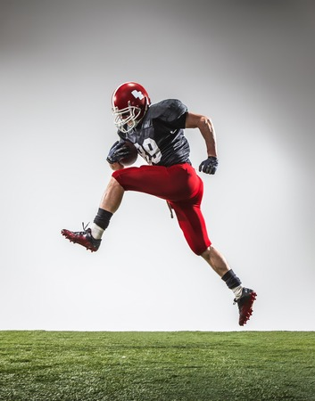 floodlit: The american football player in action on green grass and gray background. Stock Photo