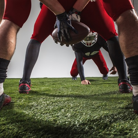 floodlit: The three american football players in action on green grass and gray background. Stock Photo