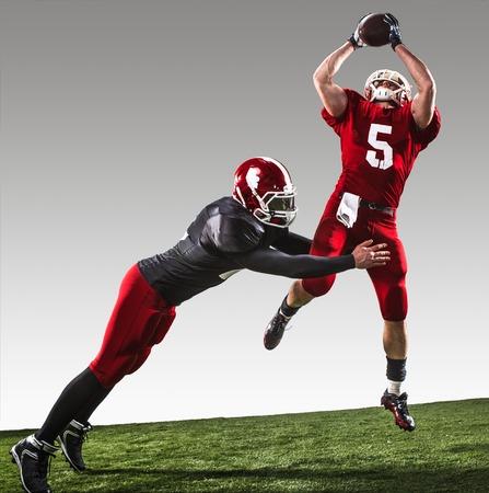 jugadores de futbol: Los dos jugadores de fútbol americano de la acción sobre la hierba verde y el fondo gris. Foto de archivo