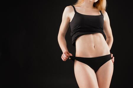 Jonge, slanke, gezonde en mooie vrouw in witte lingerie op de zwarte achtergrond
