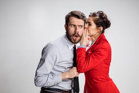 Mujer joven que dice malas lenguas a su colega el hombre en la oficina.