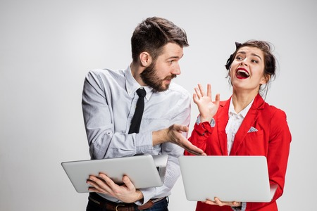 offend: The young businessman and businesswoman with laptops communicating on gray background. Stock Photo