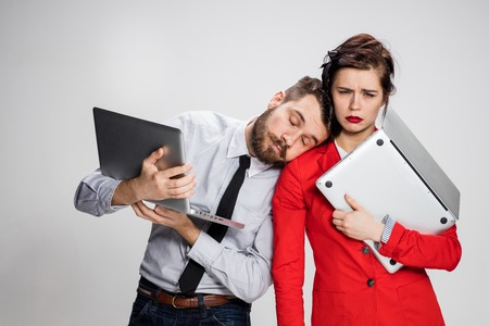 The yawning, bored and sleeping young businessman and businesswoman with laptops on gray background. Stock Photo