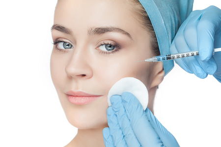 Attractive woman at plastic surgery with syringe in her face on white background Stok Fotoğraf