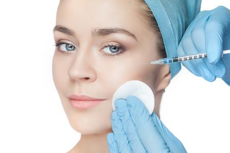 Donna attraente alla chirurgia plastica con la siringa nel suo volto su sfondo bianco Archivio Fotografico - 57591084