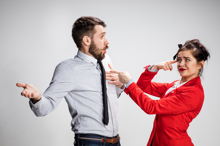 Het grappige zaken man en vrouw communiceren op een grijze achtergrond.