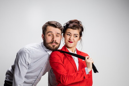 conflicting: The funny business man and woman cooperating on a gray background. Stock Photo