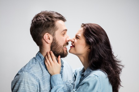 playfulness: Portrait of happy couple on gray background.