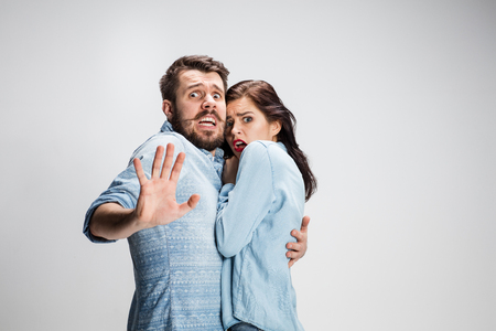 Emotionele gezichtsuitdrukking grote ogen paar, vrouw en man op zoek verrast open mond op grijs