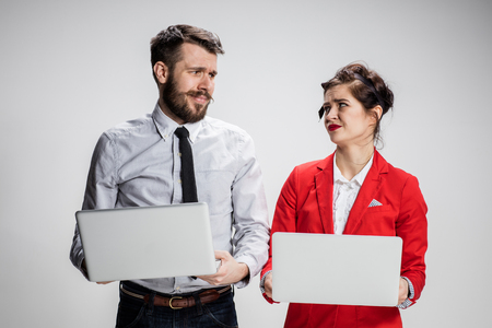 mockery: The young businessman and businesswoman with laptops communicating on gray background. Stock Photo