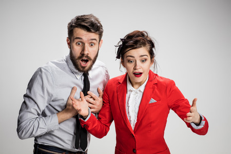 The funny surprised business man and woman smiling on a gray background.