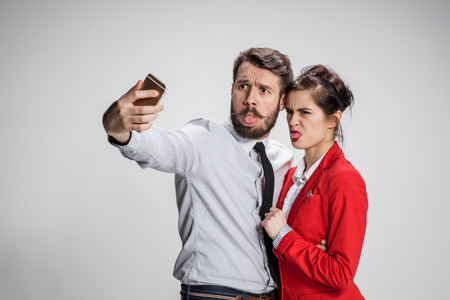 conflicting: The funny business man and woman on a gray background. Business concept