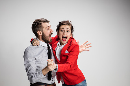 conflicting: The funny business man and woman laughing on a gray background. Business concept of relationship and victory