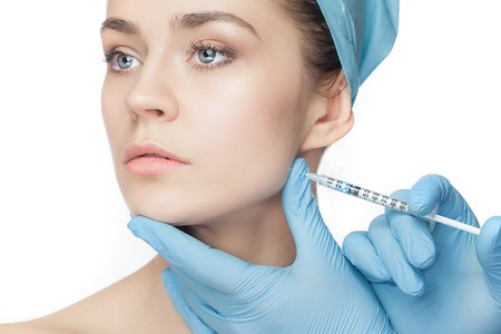 Attractive woman at plastic surgery with syringe in her face on white background Stock Photo