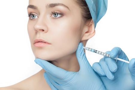 Donna attraente alla chirurgia plastica con la siringa nel suo volto su sfondo bianco