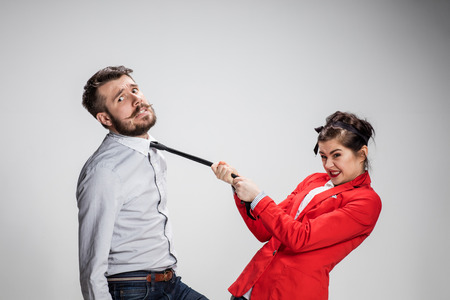 The business man and woman communicating on a gray background. Woman leading a man by his tie