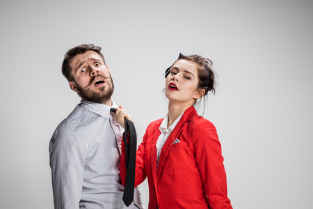 superiority: The business man and woman communicating on a gray background. Woman leading a man by his tie