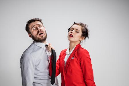 ビジネスの男性と女性のグレーの背景上で通信。彼のネクタイで男をリードする女性