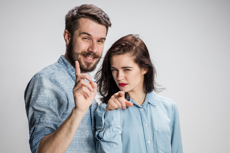 conflicting: The business man and woman on a gray background pointing fingers at the camera Stock Photo