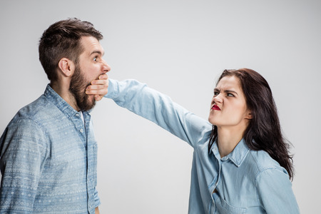 mouth couple: The young couple with different emotions during conflict on gray background. The girl opening mouth of man