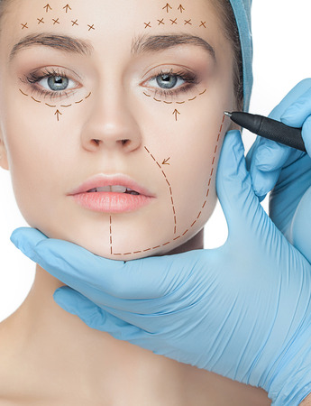 perforation: Beautiful young woman with perforation lines on her face before plastic surgery operation. Stock Photo
