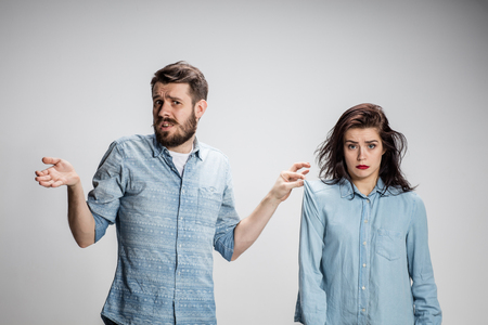 The young couple with different emotions during conflict on gray background