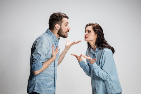 conflicting: The young couple with different emotions during conflict on gray background