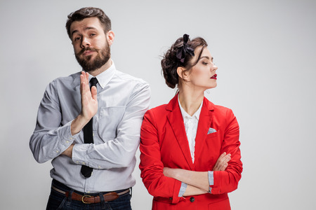 conflicting: The funny sad business man and woman conflicting on a gray background.