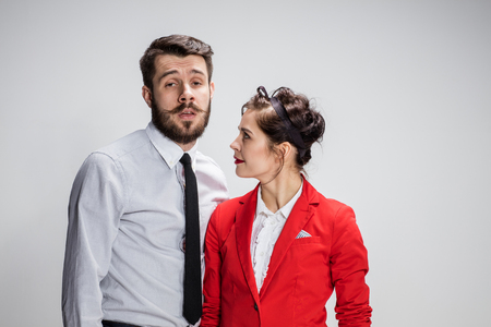 conflicting: The funny business man and woman communicating on a gray background. Business concept of relationship of colleagues